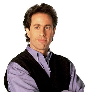 Young Jerry Seinfeld wearing a blue shirt and black coat