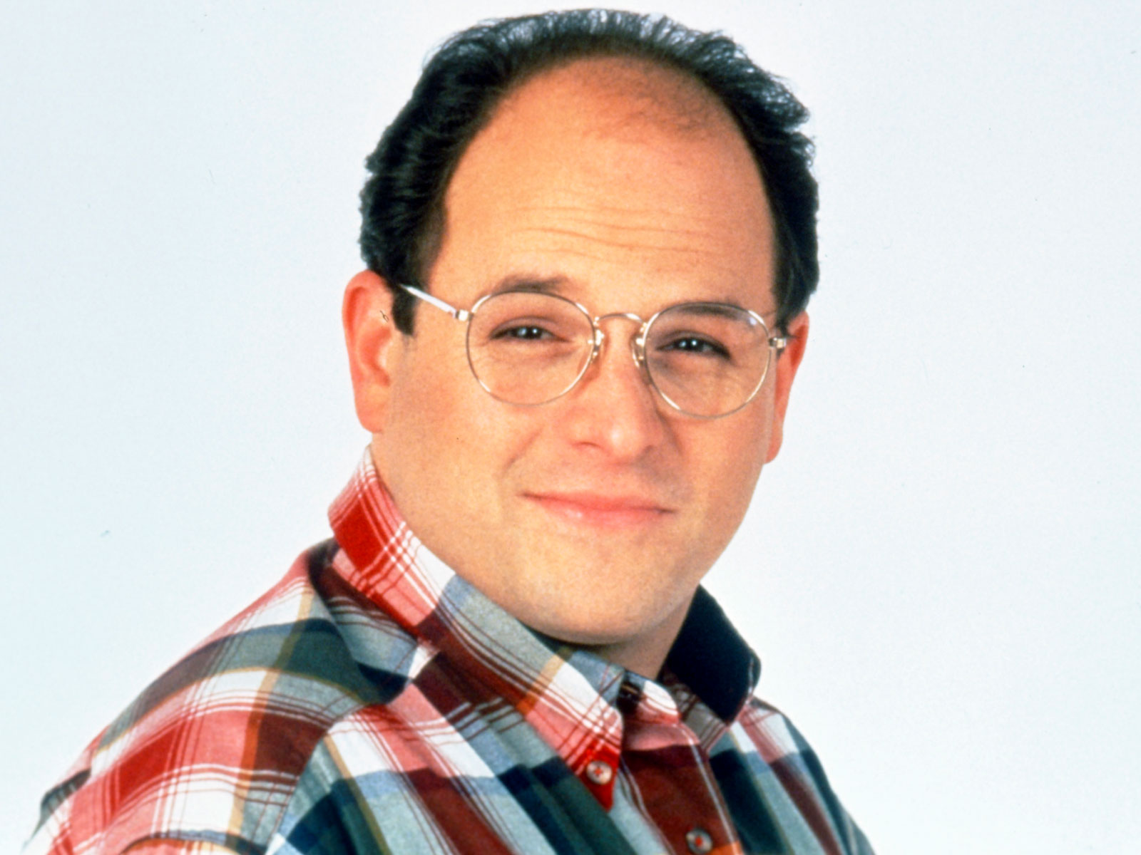 Smiling Jason Alexander wearing red and white check shirt and spectacles