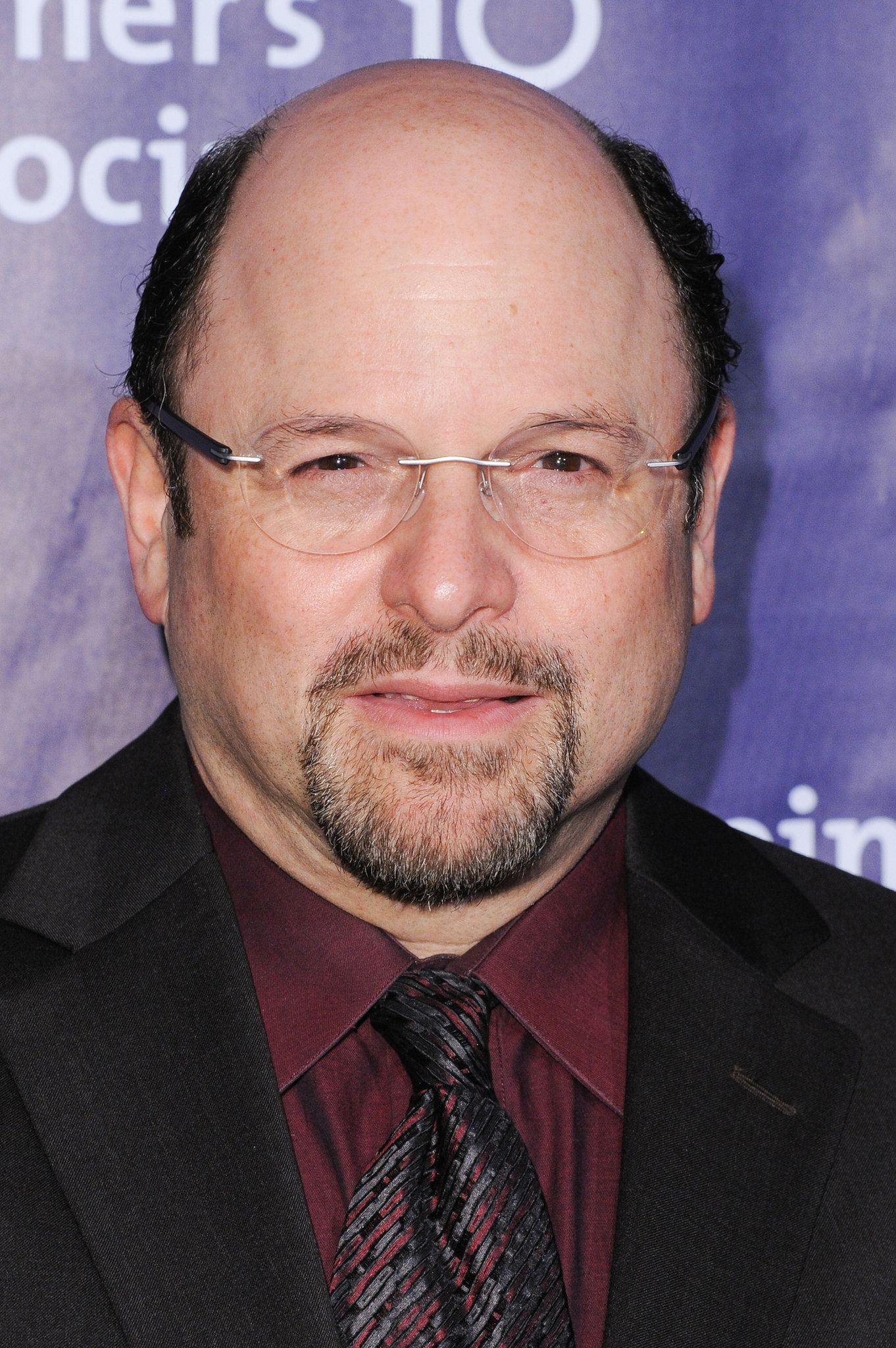 Old Jason Alexander with his bald head wearing red shirt and black coat