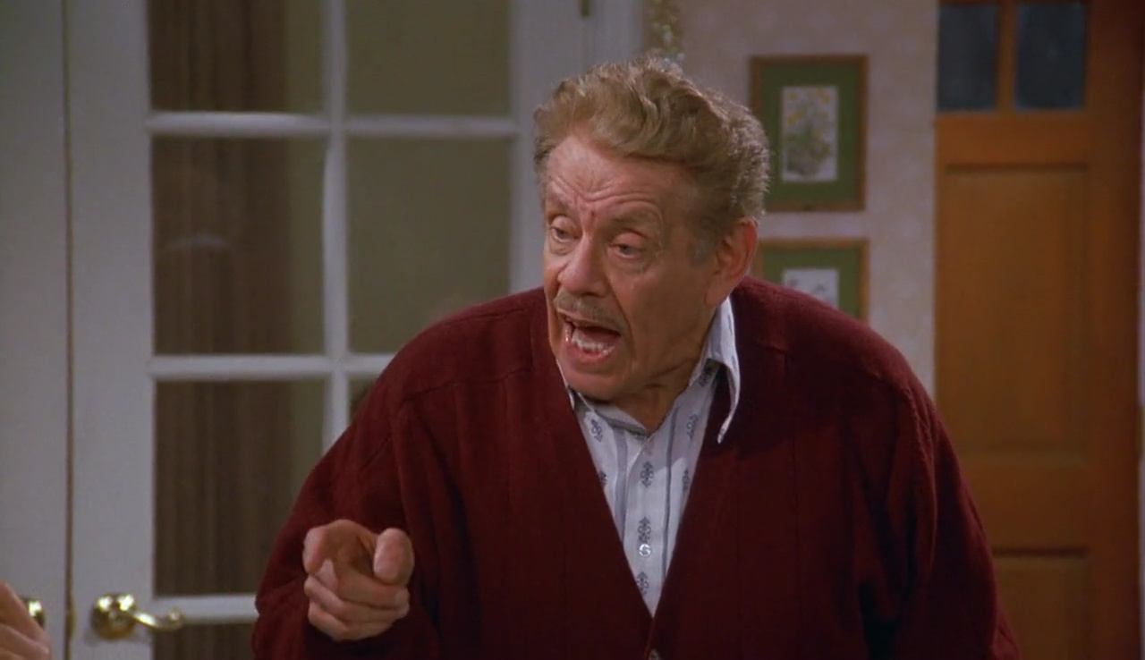 Jerry Stiller wearing a red sweater and shouting at someone in a scene of a show