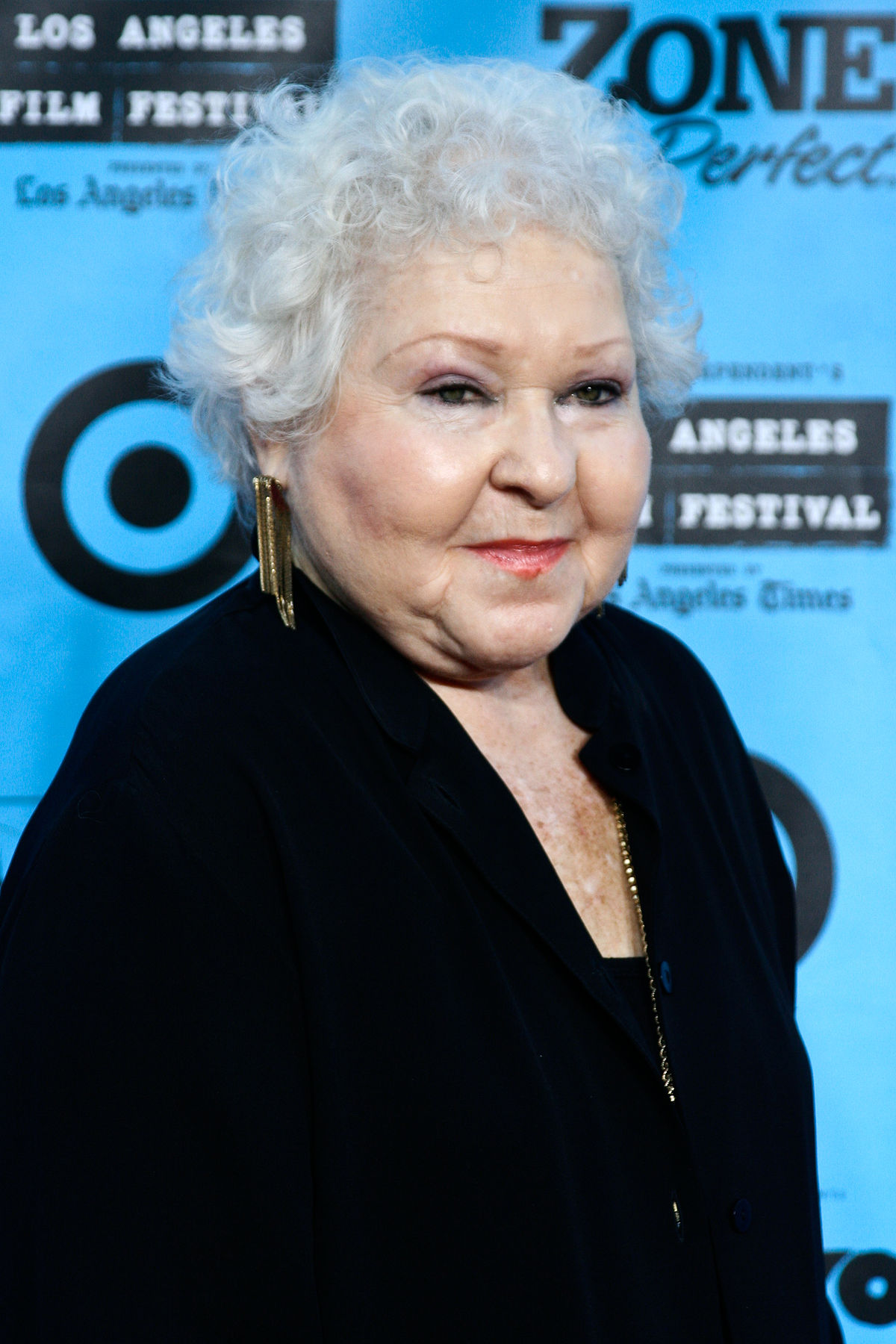 Old Estelle Harris in a white hair and long black coat