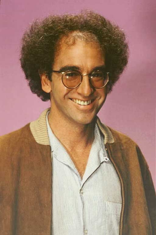 Larry David in his mid age with his curly hair wearing a spectacles