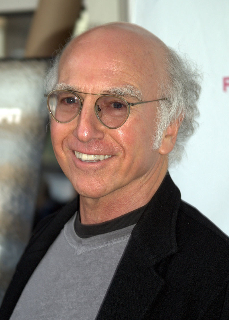 Larry David smiling in his white hair and wearing a spectacles
