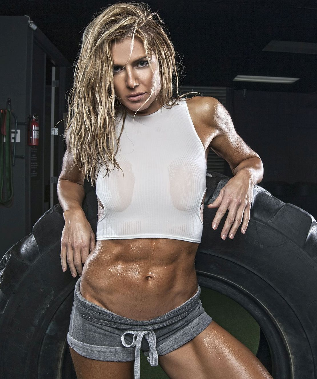 Bold and beautiful Torrie Wilson leaning against a tyre in a gym