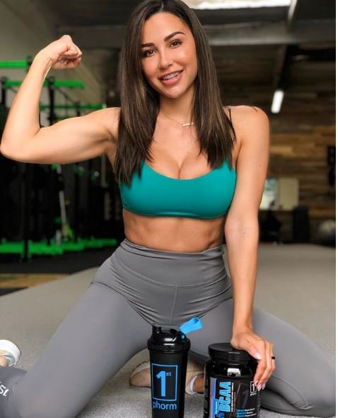 Ana Cheri promoting products. she is sitting down and their is a protein shake in front of her