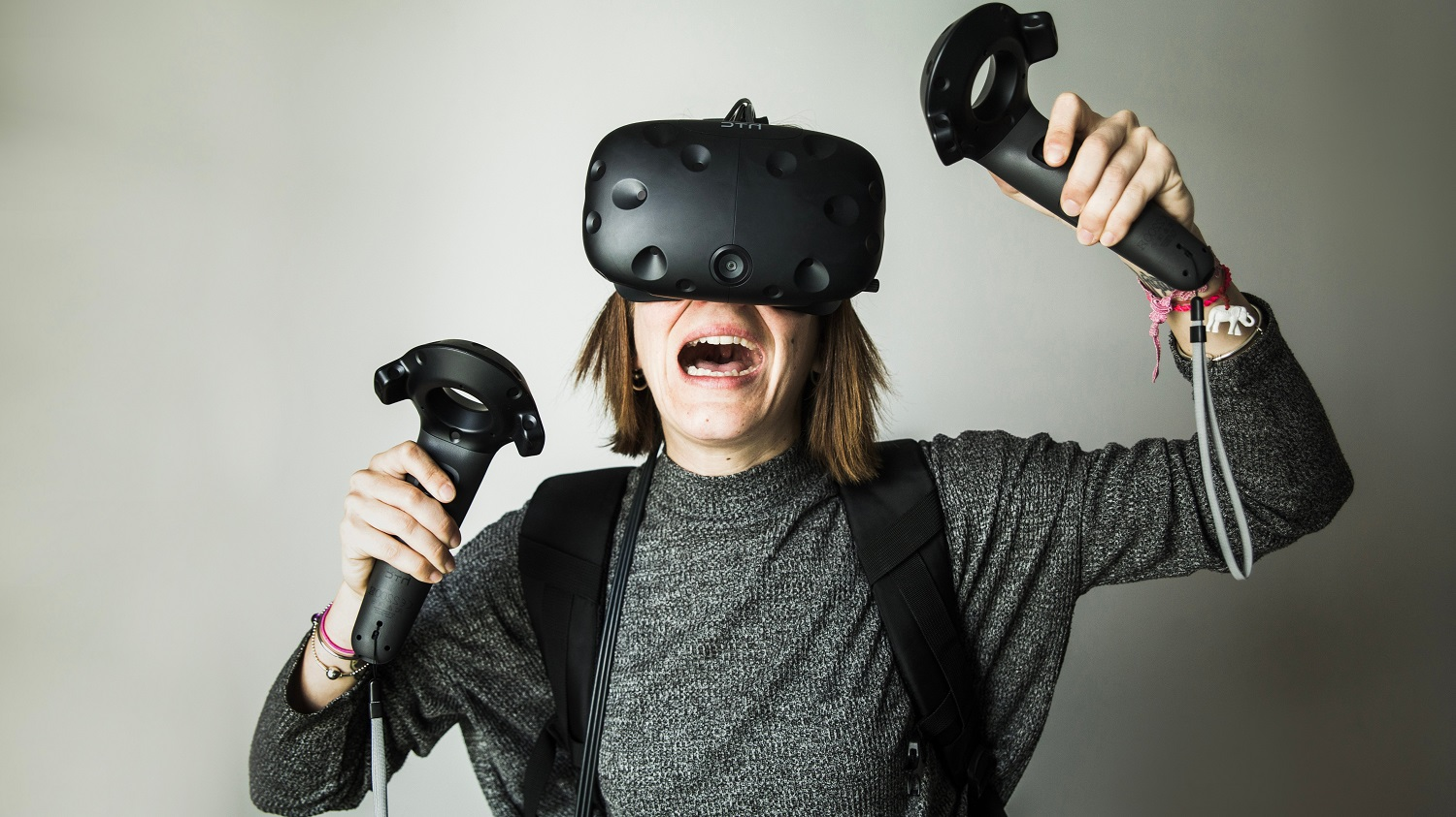 Girl wears a VR headset and holds controllers in her hands.