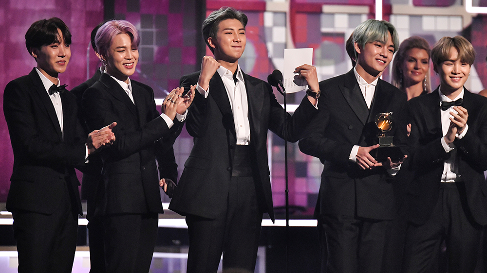 BTS members in black suits in the The Grammy presenting best R&B award to H.E.R.