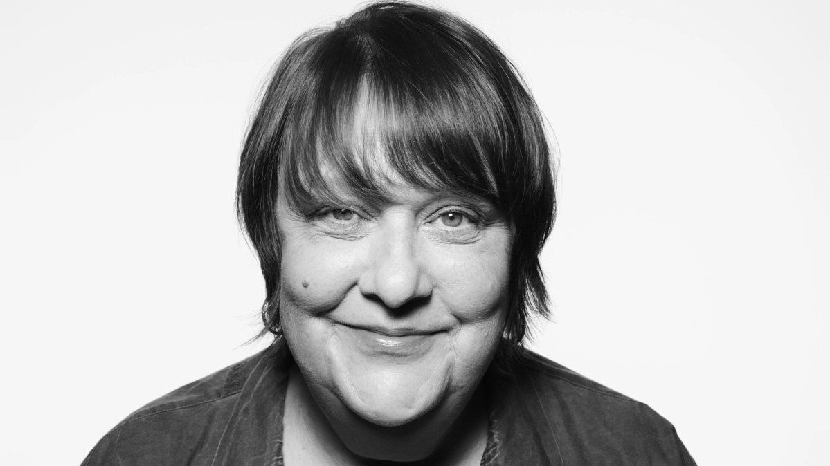 Monochrome portrait of Kathy Burke while she smiles to the camera.