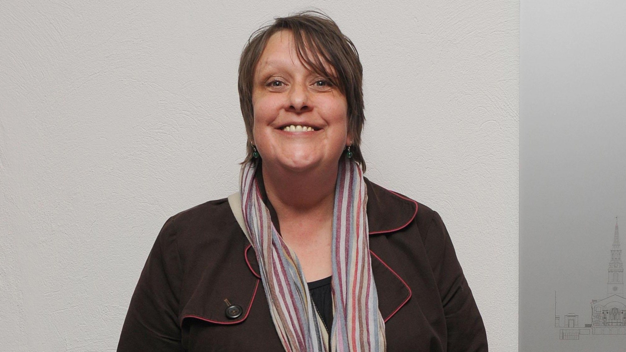 Kathy Burke smiles while she poses for a picture with a jacket and scarf.