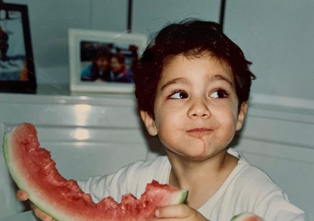 Young Chino Darin looks away as he bites into a watermelon.
